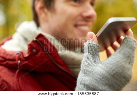 leisure, technology, communication and people concept - close up of smiling hipster man using voice command recorder or calling on smartphone in autumn