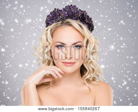 Beauty portrait of attractive blond girl with curly hair and a beautiful headband over grey winter background. Christmas concept.