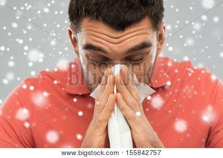 people, healthcare, rhinitis, winter and cold concept - sick man with paper wipe blowing nose over snow on gray background