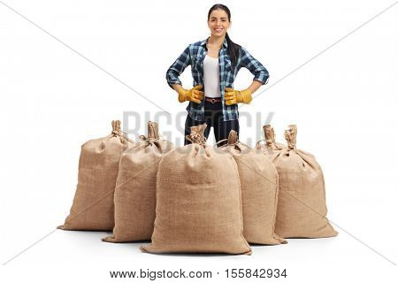 Happy female farmer standing behind a burlap sacks isolated on white background
