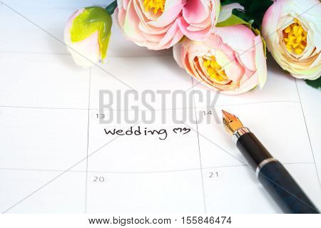 word wedding on calendar with sweet flowers and pen love concep