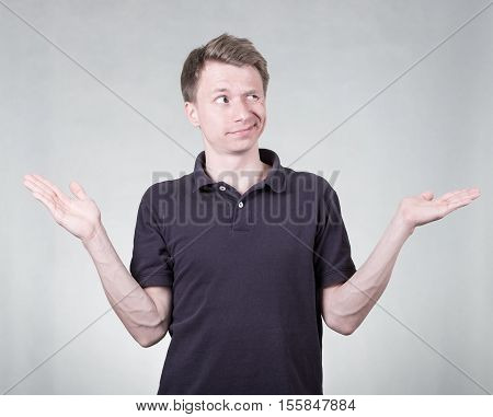 Doubtful young man on grey background isolated