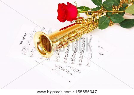 Red rose saxophone and music sheet on a white background