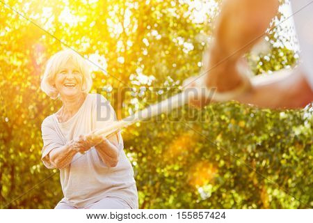 Two happy seniors playing tug of war in summer in the garden