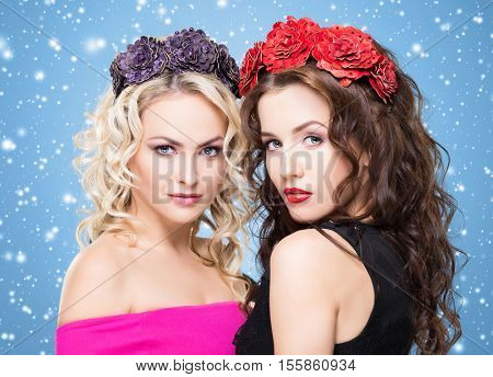 Beauty portrait of couple of attractive blond and brunette girls with curly hair and a beautiful headband over blue winter background. Christmas concept.