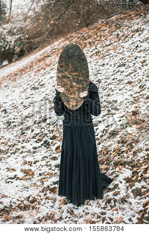 Young woman in black dress holding big oval mirror. Outdoor shot. Winter, snowy weather. Mystic gloomy gothic style. Lonliness and frustration