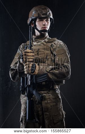 Man in military uniform with assault rifle on background of dark wall. The soldiers - our pride