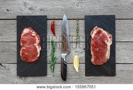Raw beef steaks on dark wooden table background, top view. Fresh juicy meat with rosemary and cutting knife on stone boards. Cooking ingredients, butcher's and grocery concept