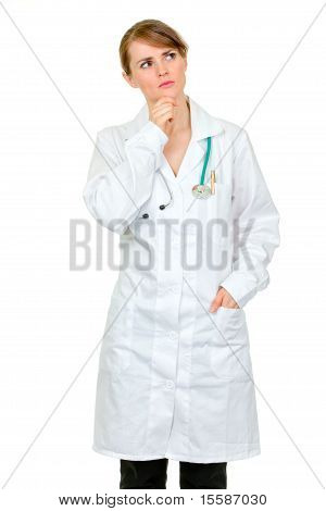 Thoughtful medical doctor woman looking up at copy space isolated on white