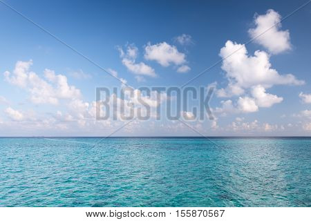 Tropical turquoise lagoon in Indian Ocean. Bright blue sky with clouds. Used a polarizing filter