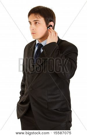 Concentrated modern businessman with handsfree isolated on white