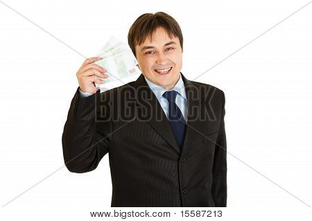 Smiling modern businessman holding euro packs in his hand isolated on white