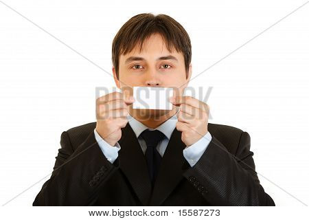 Modern businessman holding blank business card in front of mouth isolated on white
