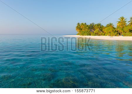 Panorama of tropical island Beach with palm trees turquoise lagoons and coral reef.