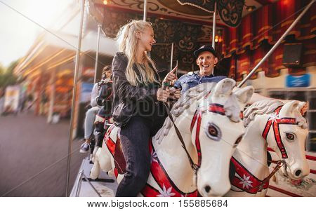 Smiling man and woman on amusement park carousel. Young couple on horse carousel ride at fairground.