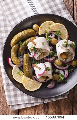 Tasty Rollmops Stuffed Olives, Onions, Pickles And Lemon Close-up On A Plate. Vertical Top View