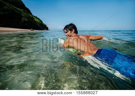 Shot of young man water surfing in sea. Male surfer in the ocean water with surf board. Enjoying holidays.