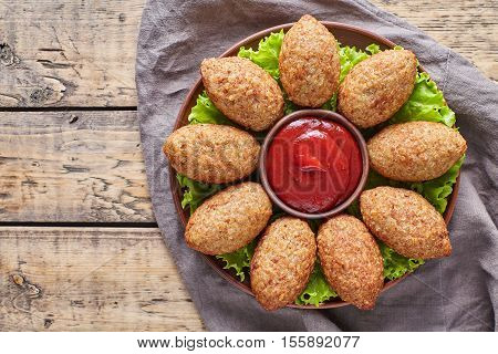Kibbeh traditional middle eastern restaurant lamb goat or camel meat stuffed bulgur kofta spicy meatball croquettes on green salad food on vintage wooden table background