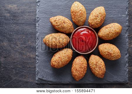 Kibbeh homemade middle eastern beef, lamb, goat or camel meat stuffed bulgur kofta spicy meatball fried croquettes dinner food on dark table background
