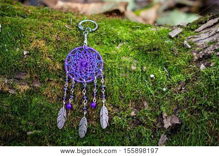 metal keychain with dream catcher handmade on the bark and mos of a tree