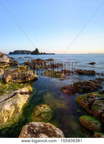 Waves lap into a rocky inlet of the Antrim Coast with Sheep Island in the background. Northern Ireland