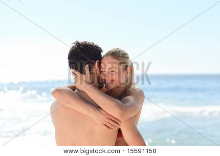 Woman hugging her boyfriend at the beach