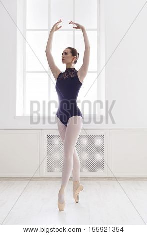 Classical Ballet dancer portrait. Beautiful graceful ballerina in black practice fifth ballet position near large window in light hall. Ballet class training, high-key soft toning. Vertical image