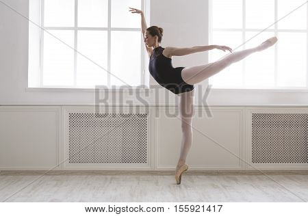 Classical Ballet dancer side view. Beautiful graceful ballerina in black practice arabesque ballet position near large window in light hall. Ballet class training, high-key soft toning.