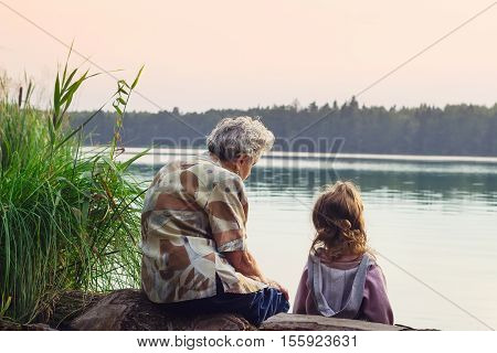 Grandmother with grandchild - senior woman and child looking at the river in warm summer day