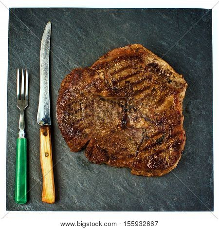 Delicious Grilled Steak Beef Shank on Black Stone Plate with Retro Fork and Knife Cross Section on White background