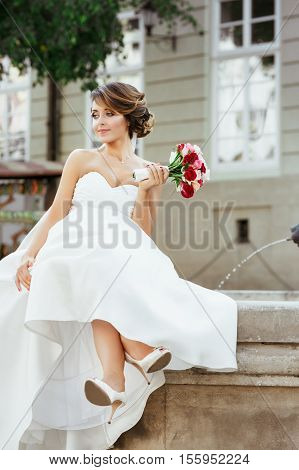 Wedding photo shooting. Bride sitting near monument in the city. Holding bouquet and looking aside. Wearing white dress, white shoes and veil. Outdoor, full body