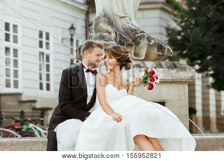 Wedding photo shooting. Bride and groom sitting near monument. Holding bouquet, smiling. Bride looking at bridegroom and man looking aside. Outdoor
