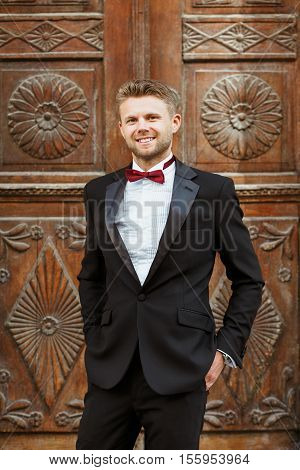 Wedding photo shooting. Bridegroom standing near wooden door and smiling. Wearing white shirt, vinous bow-knot and black jacket. Outdoor