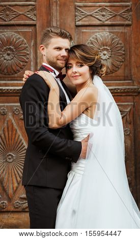 Wedding photo shooting. Bridegroom and bride standing near wooden door and embracing each other. Outdoor