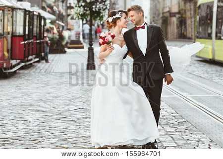 Wedding photo shooting. Bride and bridegroom walking in the city. Looking at each other, holding bouquet, embracing with one hand. Outdoor, full body. Tram, cobbled street