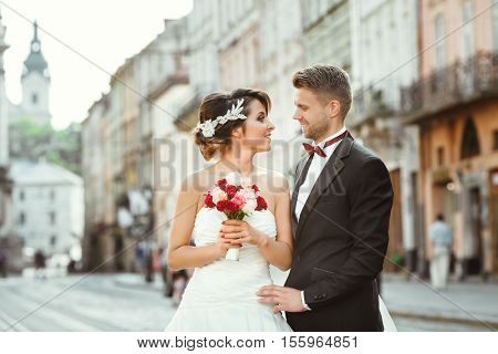 Wedding photo shooting. Bride and bridegroom walking in the city. Looking at each other, holding bouquet. Outdoor, cobbled street
