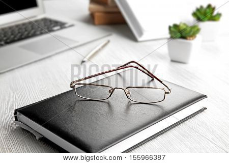 Glasses lying on notebook, close up view. Healthy eyes concept