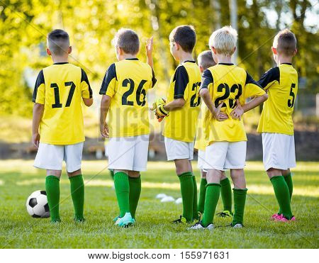 Youth football soccer training. Young boys training soccer on sports field. Group of young football players in yellow shirts. Summer soccer practice. School soccer team.