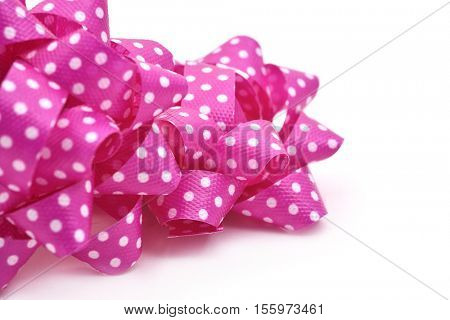 closeup of some gift puff bows made with pink ribbon patterned with white dots, on a white background