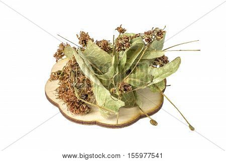 Handful of dried linden flowers (Tilia) on a wooden plate close up isolated on white background. It is used for the preparation of useful herbal tea and medicinal infusions in the herbal medicine