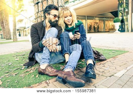 Couple of trendy hipsters using mobile phone sitting on the street at autumn season - Friends having a break relaxing outdoors and looking down to telephone - Desaturated soft vintage filter
