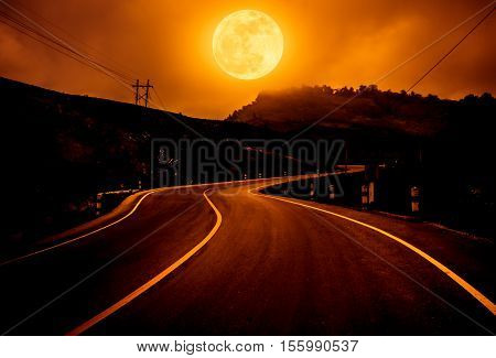 Landscape of full moon with curvy roadway in forest at national park. Outdoors at night on orange background in challenging lighting conditions. The moon taken with my own camera no NASA images used.