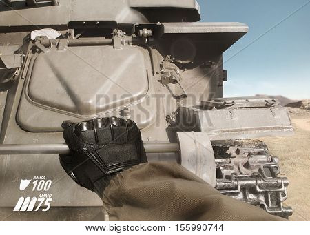 First person view soldier hand in black battle gloves & tactical jacket climbing on desert armored tank with health & armor indicator.