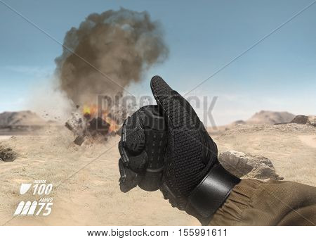 First person view soldier hand in black battle gloves & tactical jacket using hand remote to explode target on desert war scene with health & armor indicator.
