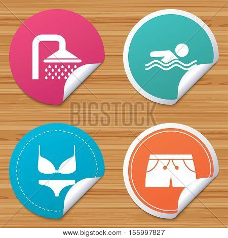 Round stickers or website banners. Swimming pool icons. Shower water drops and swimwear symbols. Human swims in sea waves sign. Trunks and women underwear. Circle badges with bended corner. Vector