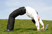 image of bending over backwards  - Businessman bending over backwards and using laptop outdoors - JPG