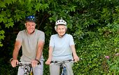 stock photo of old couple  - Senior couple mountain biking outside - JPG