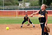 foto of fastpitch  - Young female fastpitch softball shortstop getting into ready position as pitcher releases ball - JPG