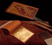 Gold leaf with burnisher, knife, brush, and icon poster