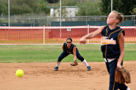 image of fastpitch  - Young female fastpitch softball shortstop getting into ready position as pitcher releases ball - JPG